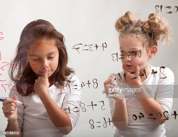 Two girls are making their mathematic assignment