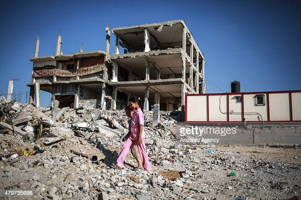 Two girls are seen near the debris of buildings in the Shuja'iyya neighborhood which was badly damaged in Israel's most recent attacks on the Gaza...