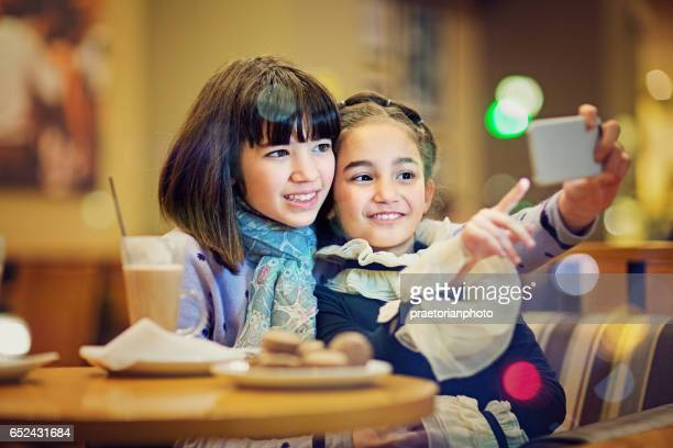 Two girls are taking selfie in the cafeteria in the night