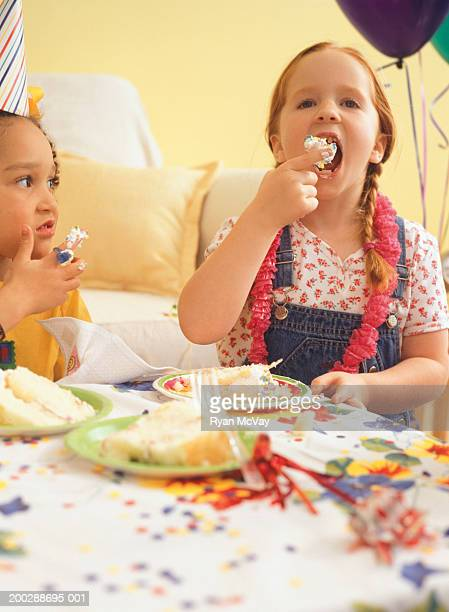 Two girls (6-7) at party, eating birthday cake