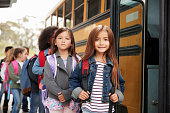 Two girls at the front of the elementary school bus queue