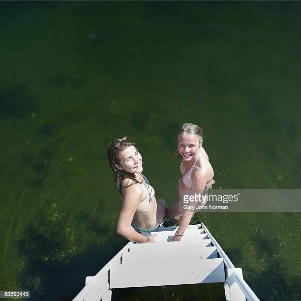 Two girls at the steps of dock feet in water
