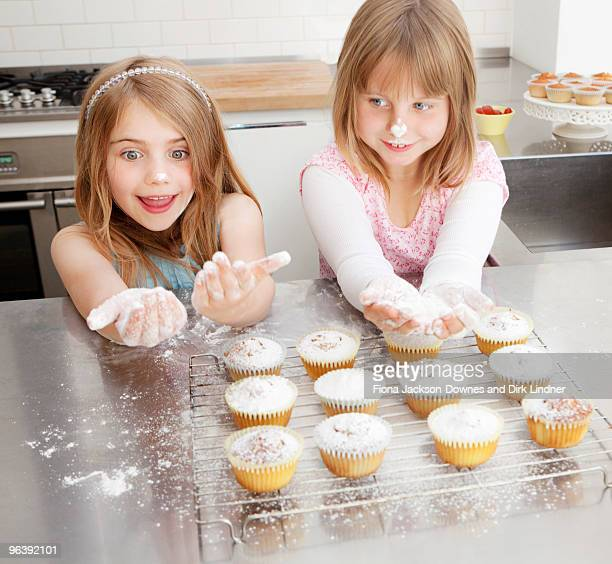 Two girls baking with icing sugar