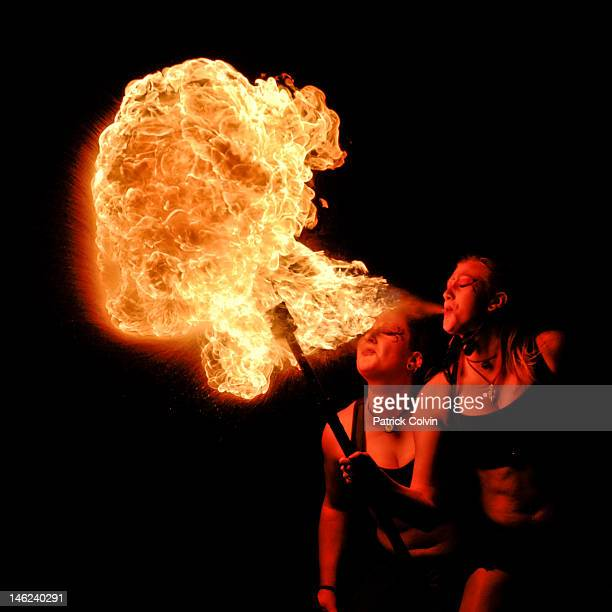 Two girls blowing fireball
