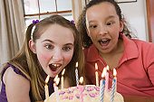 Two girls blowing out candles on a birthday cake