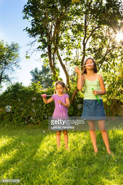 two girls blowing soap bubbles on a meadow