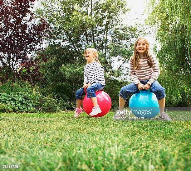 Two girls (5-8) bouncing on inflatable hoppers in garden