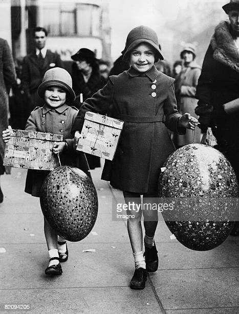 Two girls carrying huge Easter eggs in Oxford Street London England Photograph April 9th 1936 [Zwei junge Mdchen mit Ostereiern auf der Oxford Street...
