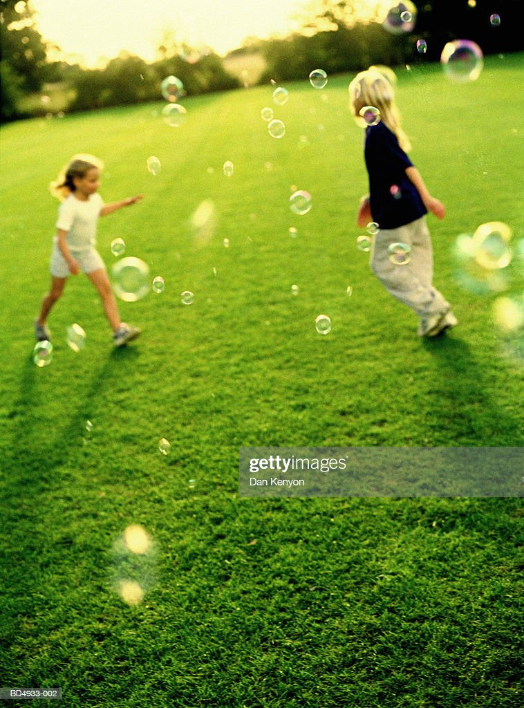 Two girls (5-9) chasing bubbles : Stock Photo