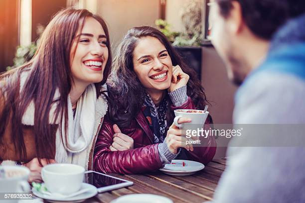Two girls chatting with a man in cafe