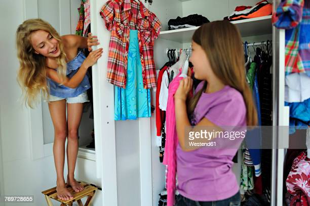Two girls choosing clothes from wardrobe
