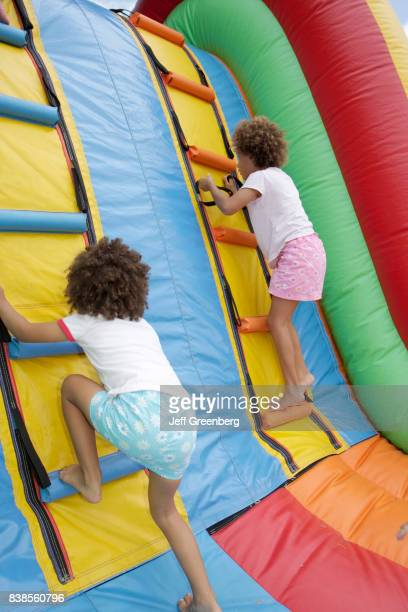 Two girls climbing a bounce slide at Miami River day