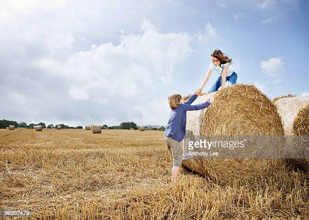 Two girls climbing on bale of hay
