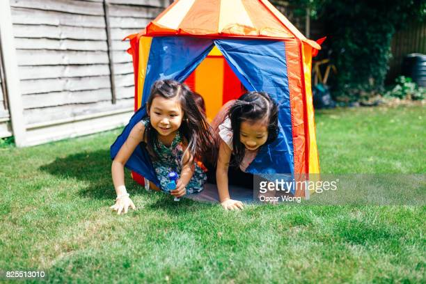 Two girls crawling out from toy tent in garden