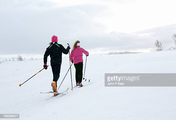 Two girls cross country skiing