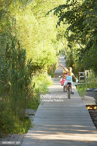 Two girls (7-9) cycling on boardwalk, one with arm raised, rear view