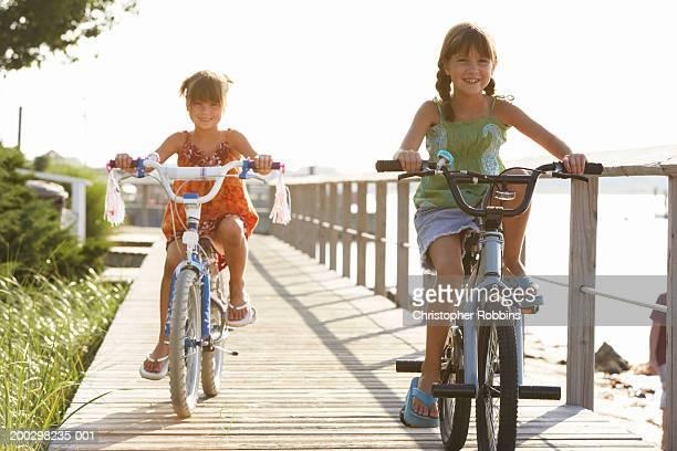 Two girls (6-9) cycling on boardwalk overlooking sea, portrait