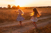 two girls dancing in a field at sunset