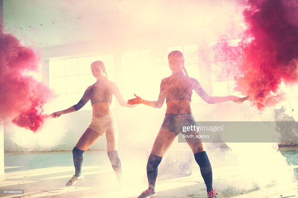Two girls dancing in the smoke : Stock Photo