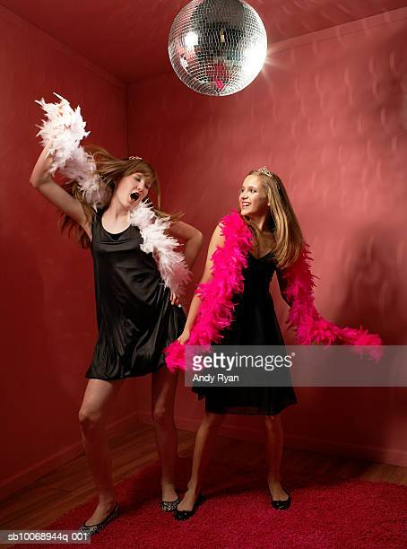Two girls (12-13) dancing under disco ball