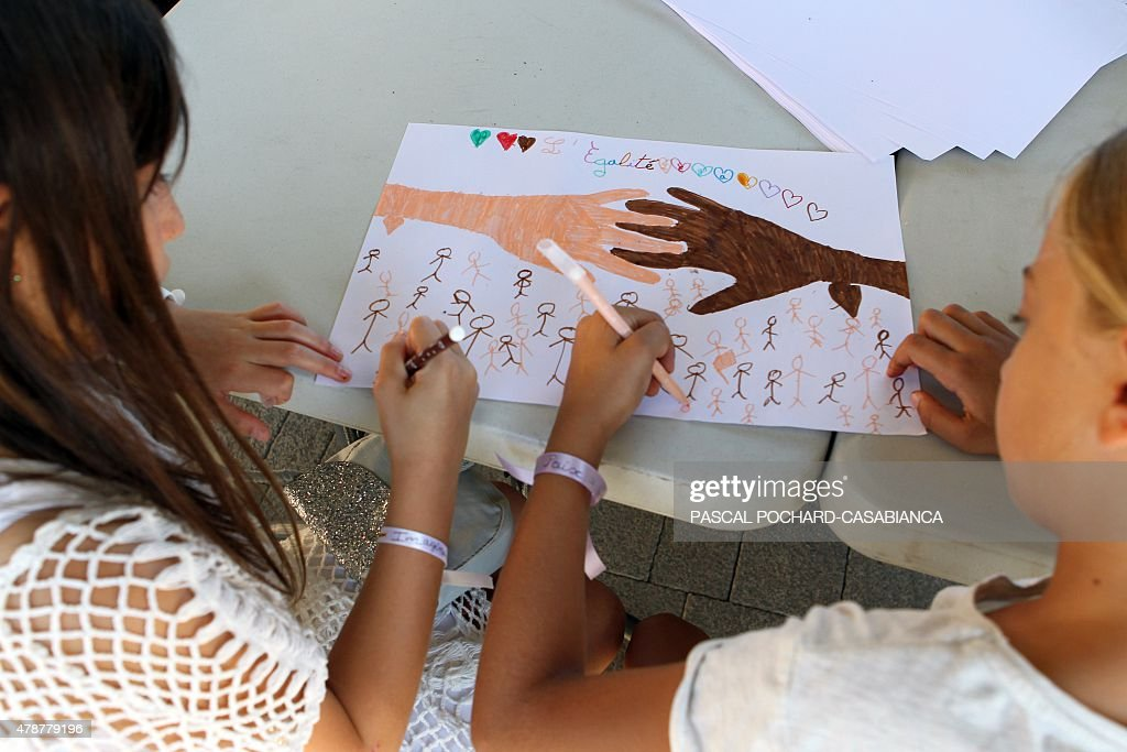Two girls draw during a meeting against racism on June 27 2015 in Ghisonaccia on the French Mediterranean island of Corsica Last week a Corsican...