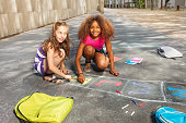 Girls draw hopscotch game on the ground near school with books and backpacks on the asphalt