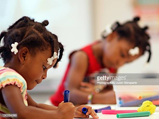 Two girls drawing and coloring in school