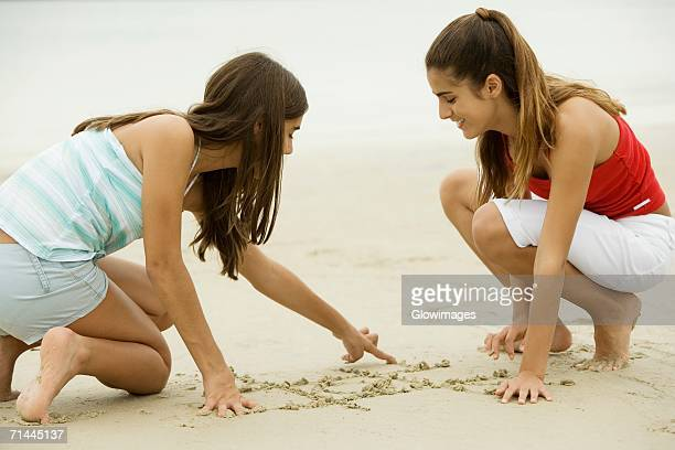 Two girls drawing in sand