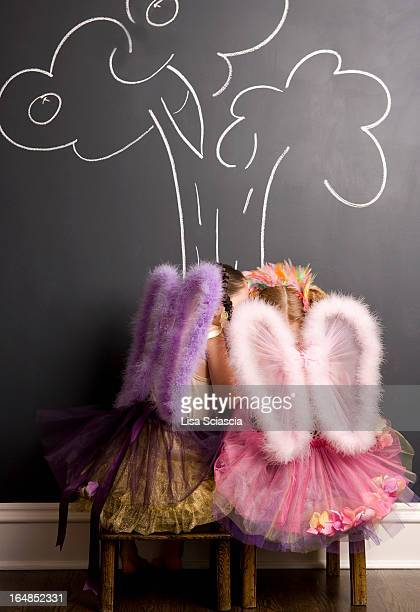 Two girls dressed as angels in front of blackboard with image of tree