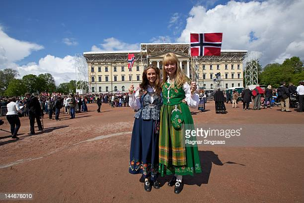 Two girls dressed in Norwegian national costume watch the Children's Parade during Norwegian National Day on May 17 2012 in Oslo Norway