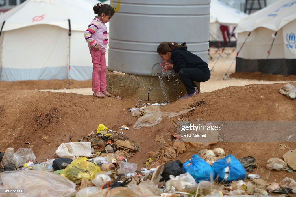 Two girls drink water as Syrian refugees go about their daily business in the Za'atari refugee camp on January 29 2013 in Mafrq Jordan Record numbers...