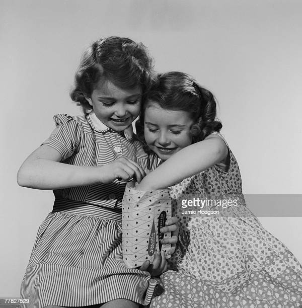 Two girls eagerly sharing a bag of sweets circa 1960