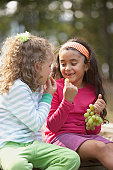 Two girls eating grapes