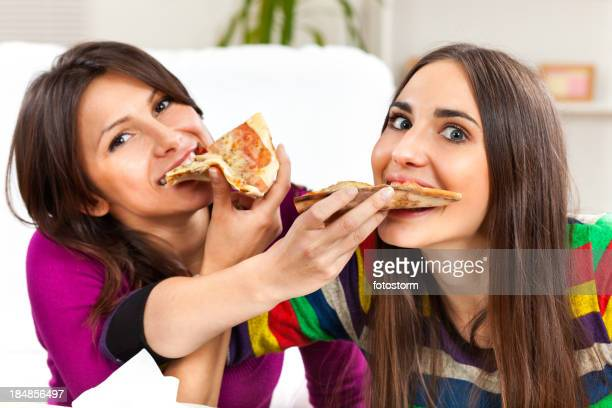 Two girls eating pizza together