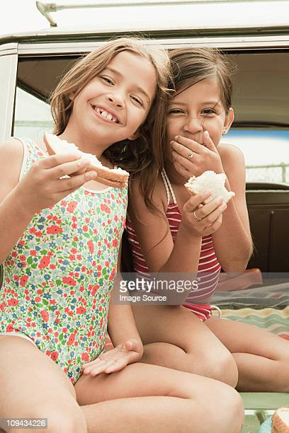 Two girls eating sandwiches on car boot