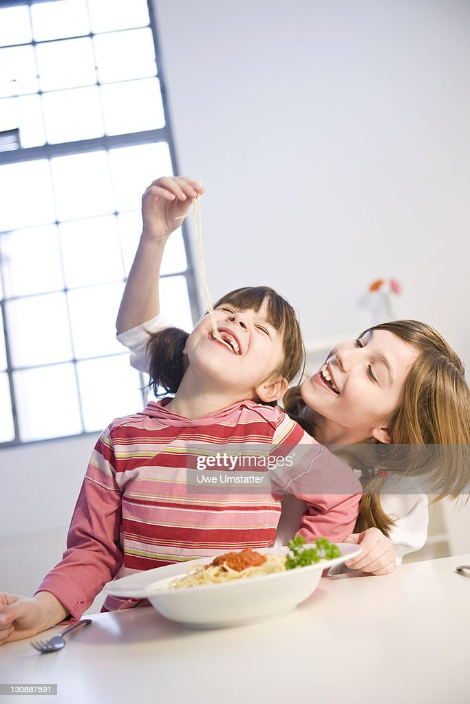 Two girls eating spaghetti together : Stock Photo