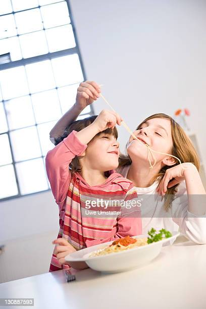 Two girls eating spaghetti together