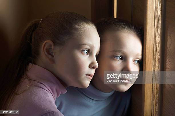 Two girls eavesdropping on door, close-up