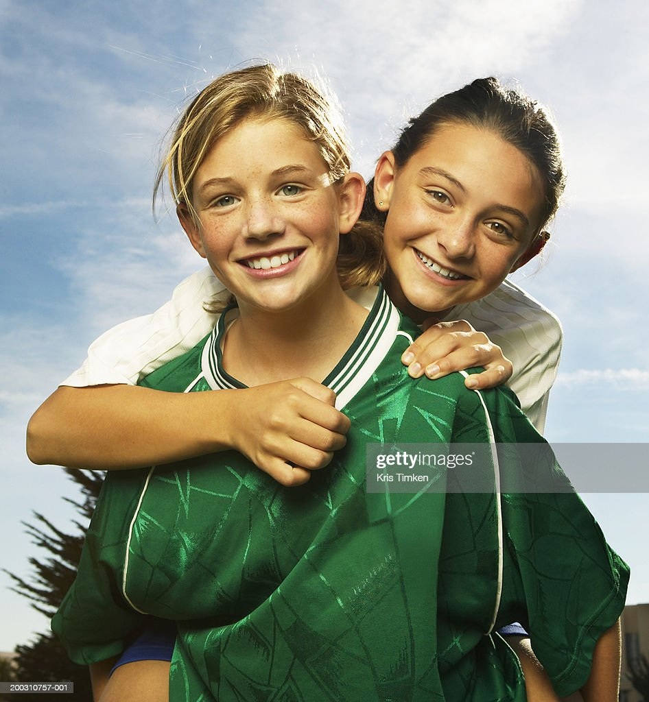 Two girls (10-12) embracing, wearing soccer uniforms, smiling : Stock Photo