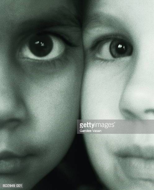 Two girl's faces (5-7) cheek to cheek, close-up (B&W)