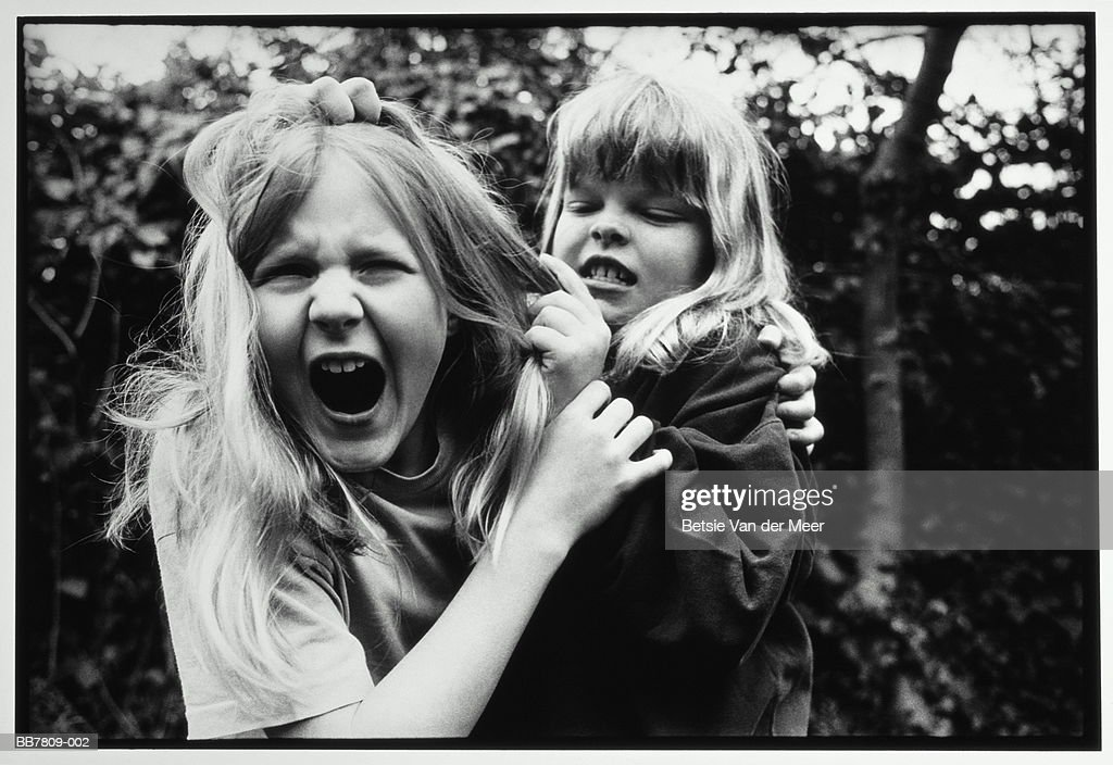 Two girls (9-11) fighting outdoors (B&W) : Stock Photo