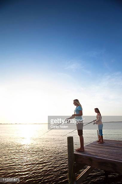 Two girls fish off a pier on the Santa Rosa Sound, Pensacola Beach, Florida at sunset.