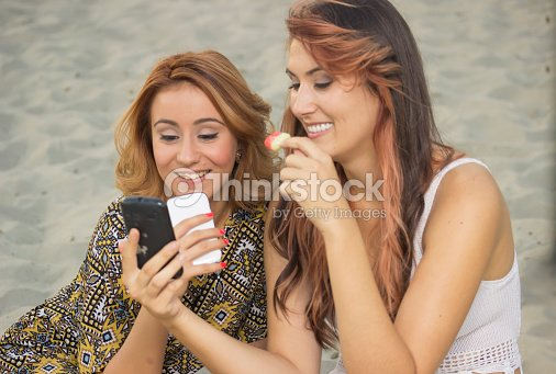 Two Girls Friends Eating Ice Cream And Using Mobile Phone Stock Photo