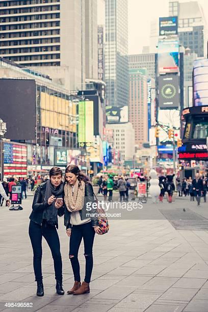 Deux filles amis naviguant sur pied, avec le GPS téléphone portable.