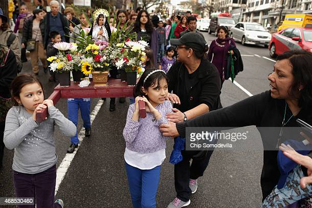 Two girls get guidance from fellow worshipers as they carry a statue of Mary the mother of Jesus Christ during the Via Crusis or 'Way of the Cross'...