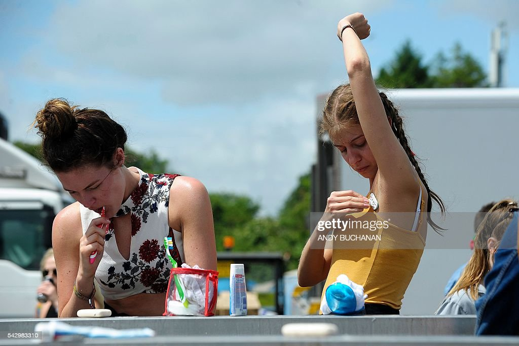 Two girls get ready for the day ahead on day four of the Glastonbury Festival of Music and Performing Arts on Worthy Farm near the village of Pilton in Somerset, South West England on June 25, 2016. / AFP / Andy Buchanan