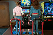 Two girls get ready to play an electronic dancing game at an amusement arcade at Alton Towers Alton England UK