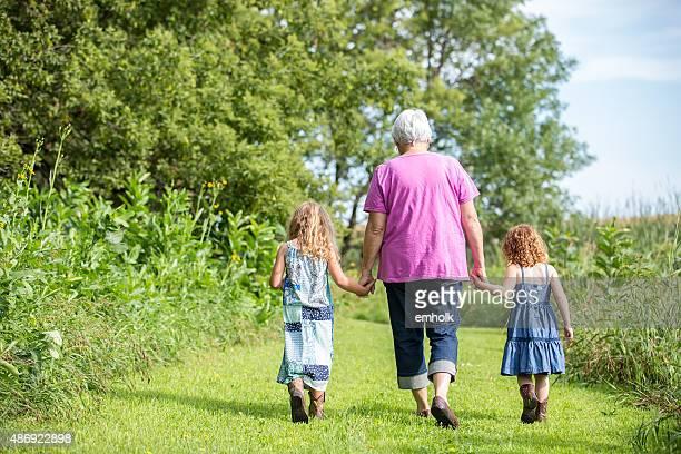 Dos chicas & Grandma caminando sobre hierba Trail