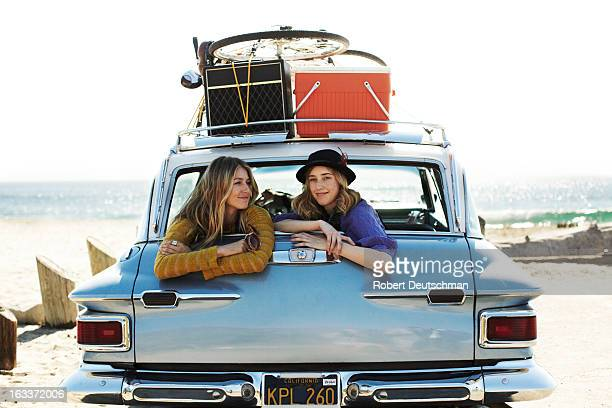Two girls hanging out in the back of a car.