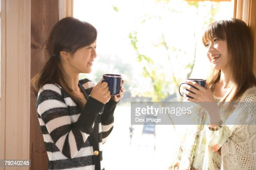 Two girls having coffee, by the window : Stock Photo